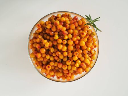 Glass cup with sea buckthorn berries on a white background. Top view. Ingredients for Herbal Tea.