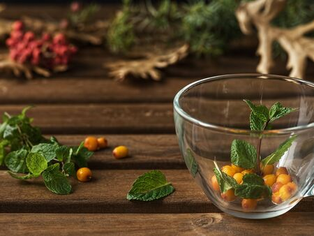 Useful herbal tea with sea buckthorn and ginger. Glass cup with mint leaves and sea buckthorn. Close-up.