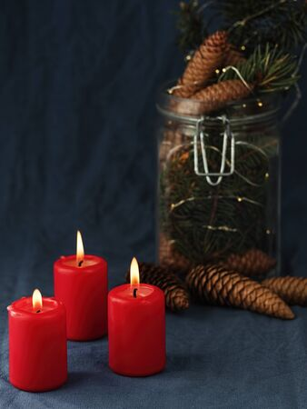 Advent, burning red candles. Alternative Christmas tree with a garland. Close-up. Stock Photo