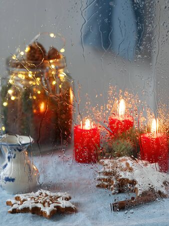Christmas window. Candles, garlands, Christmas decoration, gingerbread cookie. Close-up, it is raining. Vertical orientation. Christmas atmosphere Stockfoto