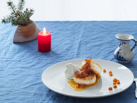 Cheesecakes or curd pancakes with cream and sea buckthorn jam on a white plate, on a blue tablecloth. Vintage gravy boat. ?andle. Homemade ?ottage cheese fritters. Tasty breakfast. Closeup. Zdjęcie Seryjne