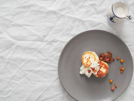 Cheesecakes or curd pancakes with cream and sea buckthorn jam on a gray plate, on a white tablecloth. Vintage gravy boat. Homemade ?ottage cheese fritters. Tasty breakfast. Top view. Copy space.