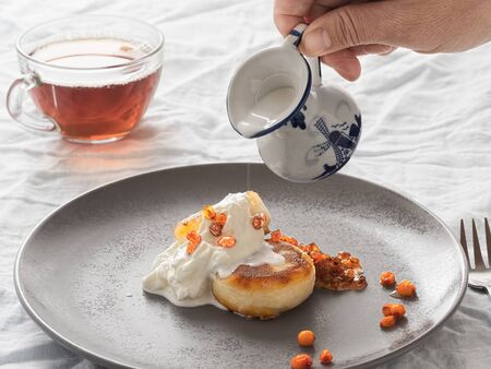 Cheesecakes or curd pancakes with cream and sea buckthorn jam on a gray plate, on a white tablecloth. Vintage gravy boat and cup of tea. Homemade ?ottage cheese fritters. Tasty breakfast. Closeup.