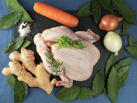 Raw chicken with vegetables on a black stone board, located on a blue tablecloth. Top view. Spices for cooking. Foto de archivo - 135502555
