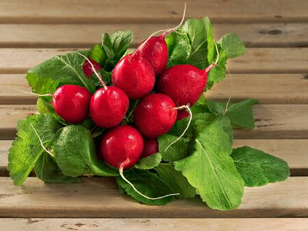 Fresh radish on a wooden brown background on radish leaves. Close-up. Selective focus on root crops. Horizontal orientation.