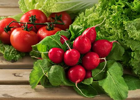 A bunch of radishes, a bunch of ripe tomatoes. Fresh chinese cabbage and salad. Drops of water on vegetables. Close-up. Selective focus on radish. Horizontal orientation. Foto de archivo - 135502599