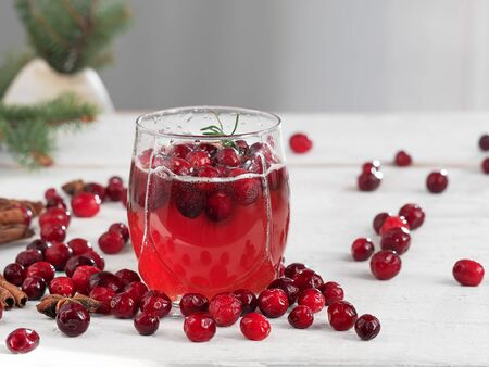 Fresh cranberry drink in a glass cup on a wooden white background. Close-up. Horizontal orientation. Cranberries and spices on the table.