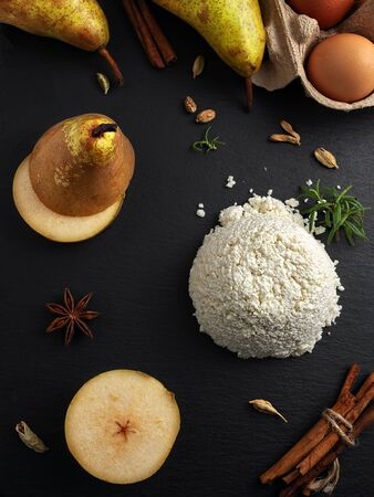 Ingredients for making homemade pie with ricotta cheese, cardamom, cinnamon and pear. Home upper view. Vertical orientation. Black stone background.