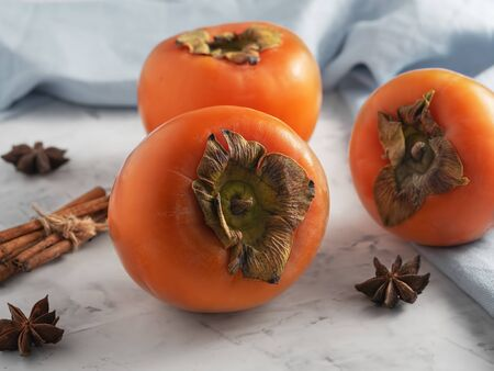 Delicious fresh persimmon fruit on a gray table. Close-up. Ingredients for persimmon jam.