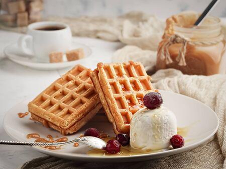 Gaufres de Liège au caramel, fruits rouges et glace. Gaufres maison avec une délicieuse sauce au caramel sur une assiette. Mise au point sélective, orientation horizontale. Fermer. Dessert sucré.