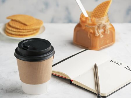 Paper cup with coffee or hot drink on the table. Notepad with a wish sheet. Close-up, selective focus on the notepad. Near the bank with caramel and waffles. Tasty dessert, holidays.