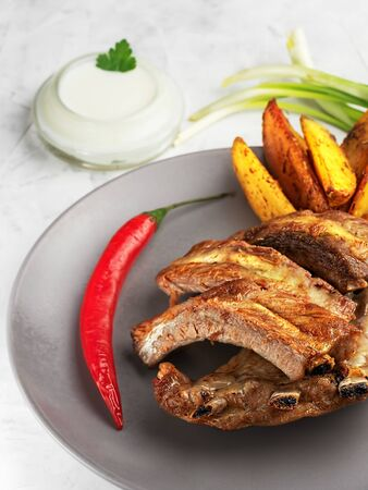 Grilled ribs with idaho potatoes and vegetables on the plate, on the grey background. Shallow depth of field. Vertical orientation, close-up.