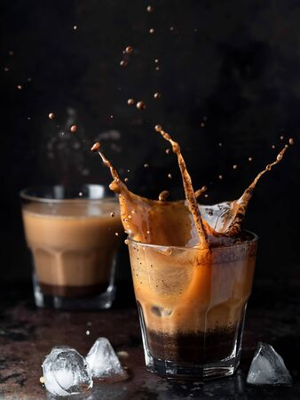 Splash in a glass with ice coffee on a dark background. Refreshing iced cappuccino drink with ice cubes. A wave of cold drink. Close up, vertical orientation, space for text. Shallow depth of field.