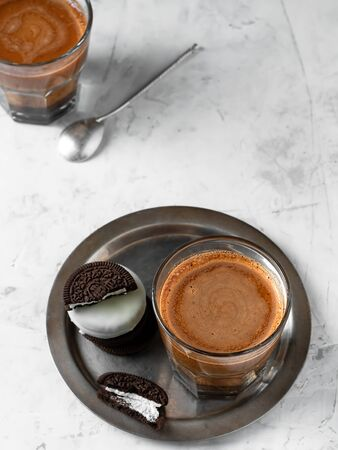 Glass of coffee with milk on a metal dish with chocolate chip cookies. Coffee is located on a light gray background. Top view, place for text, vertical orientation. Breakfast or snack concept