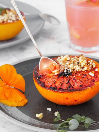 Baked grapefruit with brown sugar on a saucer decorated with violet, walnut and mint . Vertical orientation, close up. Paleo diet, grilled oranges or grapefruits.