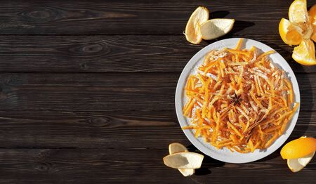Candied orange peel in sugar is a favorite treat for children and adults. Image of homemade candied oranges peel and orange on the dark wooden table. Top view, copy space