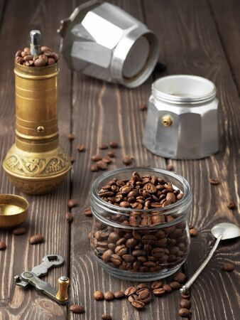 Roasted coffee grains in a glass jar and scattered coffee grains on a wooden brown table. A hand mill and a coffee pot (la moka) in the background. Close Up, concept of traditional coffee preparation. Фото со стока