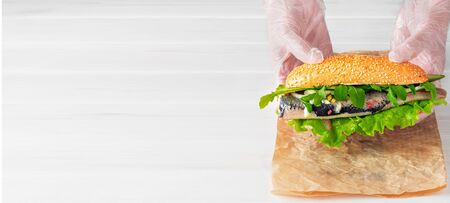 Cook's hands lay a herring fillet sandwich with onions, cucumber and salad on paper. White wooden background with copy space for text. Traditional street food in scandinavian cuisine. Stockfoto