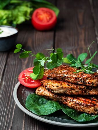 Roasted turkey fillet with bright appetizing fried crust with spices and spring herbs on a black plate, old dark wooden table. Rustic style, close-up.