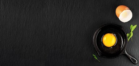 Raw chicken egg broken in a cast iron or steel pan, on a dark stone background. Top view of a bright yolk, next to the shell and leaves of arugula, copy space for recipe. Breakfast or lunch concept