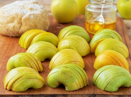 Fresh green apples cut into slices on a wooden board. Against the background of dough and honey, the process of making French galette. Close-up