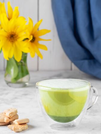 Hot matcha latte in a glass cup on a light gray table, next to crackers and a vase with blooming sunflowers. Close-up, shallow depth of field. Banco de Imagens