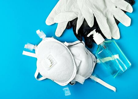 Respiratory protection respirator and latex gloves, antiseptic gel - personal protective equipment, provide protection against the spread of infection. Top view, bright blue background