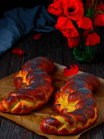 Homemade wicker challah for Shabbat. Homemade sweet Finnish Pulla or Zopf bread with poppy seeds and saffron on a baking sheet, close up. Blooming poppies on a wooden table.