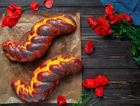 Homemade wicker challah for Shabbat. Homemade sweet Finnish Pulla or Zopf bread with poppy seeds and saffron on a baking sheet, flat lay. Blooming poppies on a wooden table.