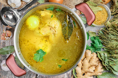 Chicken broth with vegetables and spices in a saucepan, ingredients for soup on a wooden table. Healthy healthy chicken soup warming in frost, flat lay Reklamní fotografie