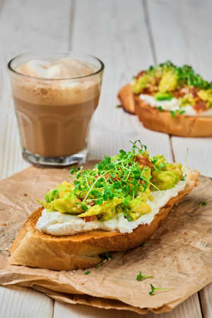 Close-up of avocado sandwich with cream cheese, microgreens and sesame seeds on paper lining. Glass with cappuccino, selective focus. Breakfast concept. Vegetable toast Banco de Imagens