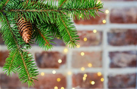 Festive Christmas card with a branch of a Christmas tree on a background of a brick wall decorated with a garland, selective focus. Christmas template for banner or postcard, close-up