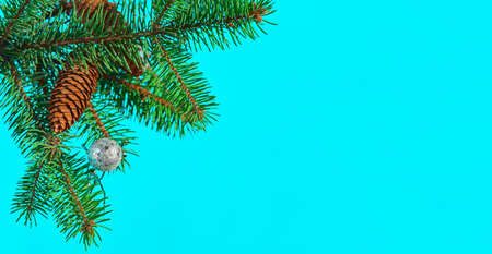 Festive Christmas card with a fir-tree branch with cones and a toy on a turquoise background, selective focus. Christmas or New Year template for banner or postcard
