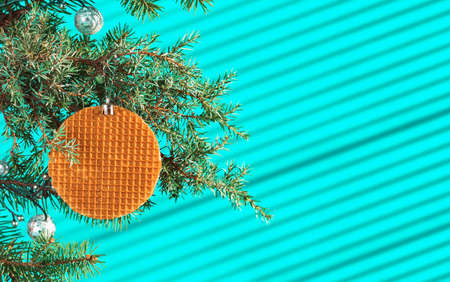 Festive Christmas card, banner or postcard with branch of Christmas tree with cones and decorated with waffle on turquoise background, streaks of light from the sun on the background, selective focus