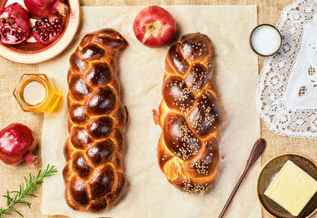 Challah bread, freshly baked sweet braided bread on parchment, burlap background. Pomegranates, apples, butter and honey for bread on the table. Top view, product mockup, hanukkah celebration