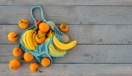 Shopping for groceries without plastic bags. Zero waste concept. Eco-friendly natural reusable bag with organic fruit oranges and bananas. Top view with copy space, wood background