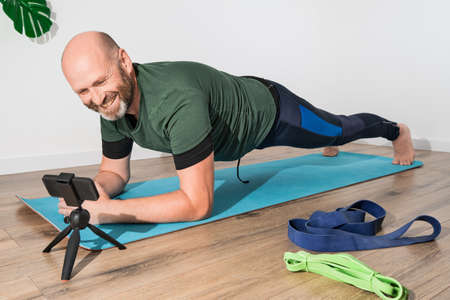 Adult man in sportswear makes a plank on the mat in front of a smartphone during an online workout. He trains at home during isolation. Sport, fitness and healthy lifestyle concept Stock Photo
