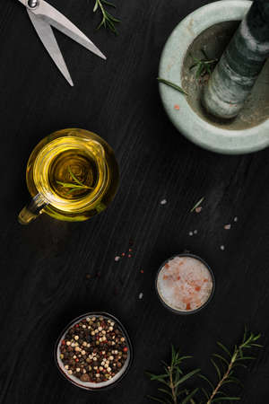 Layout of products for cooking seasoning in a marble mortar. Composition with sea salt, rosemary, olive oil and various types of pepper on a dark wooden background, top view