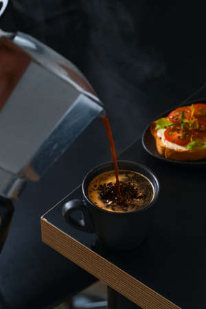 Hot fresh espresso coffee is poured into a cup from a geyser coffee maker. Bar table, cafe breakfast idea, cheese and tomato toast or antipasto. Dark moody background Stock fotó