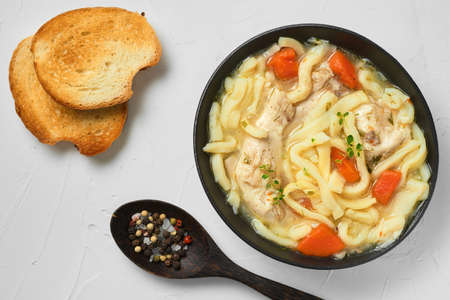 Homemade chicken noodle soup with vegetables and spices in a bowl, top view, white concrete background. Healthy food concept. Bread and spices in a wooden spoon on the table
