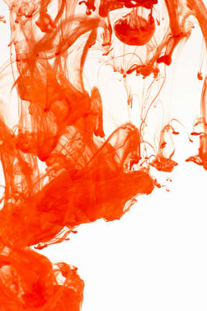 Abstraction on a white background, orange paint in motion, close-up, color drop into water