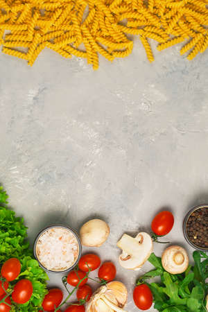 Pasta and Italian food ingredients for cooking lunch, top view. Fusilli spaghetti with various ingredients - tomatoes, arugula, mushrooms and spices. Gray background, flat lay with space for text