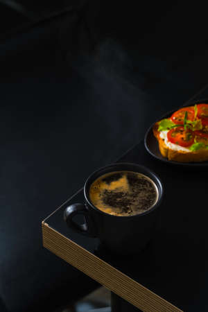 Cup with strong coffee ristretto on a bar table, an idea for breakfast in a cafe, toast with cheese and tomatoes or antipasto. Dark moody background