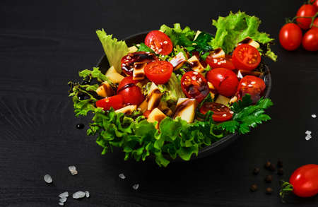 Tomato salad with lettuce, goat cheese, fresh vegetables, sesame seeds and olive oil on a black wooden table. Close-up. Healthy wholesome food