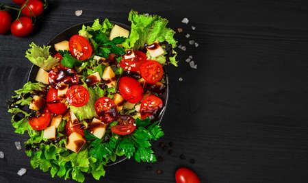 Tomato salad with lettuce, goat cheese, fresh vegetables with sesame seeds and olive oil on a black wooden table. Top view with copy space. Healthy vegetarian food, banner