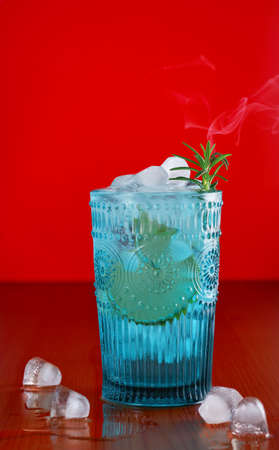 Gin and tonic, alcoholic drink with lime, rosemary and ice on rustic table, bright red background. Blue glass tumbler, smoke rises above the rosemary branch. Refreshing summer drink. Selective focus
