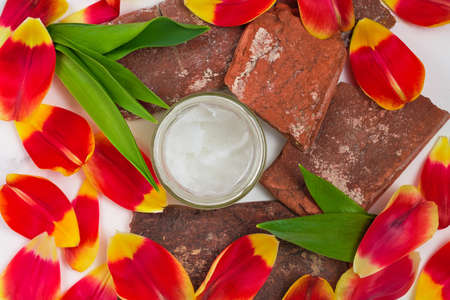 Coconut oil in a jar on a white background, layout. Top view of organic oil surrounded by tulip petals. Cosmetic spa treatments, skin, body care concept. Selective focus