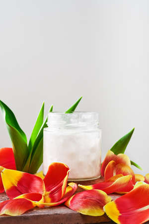 Coconut oil in a jar on a white background surrounded by tulip petals, close-up with copy space. Cosmetic and wellness spa treatments, skin and body care concept. Selective focus on the bank
