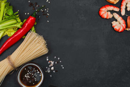 Ingredients for making fried noodles with shrimp, seafood, soy sauce and spices are placed on a black stone background. Top view, flat minimal design, asian food concept Stock fotó