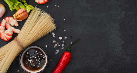 Layout of ingredients for making fried noodles with shrimp, seafood, soy sauce and spices are placed on a black stone background. Top view, flat minimal design, asian food concept